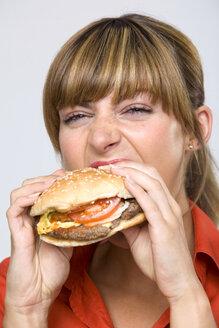 Young woman eating hamburger - WESTF01314
