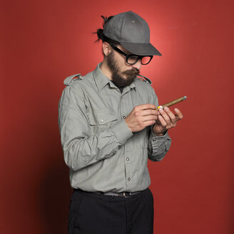 Mature man holding cigar against red background - JL00140