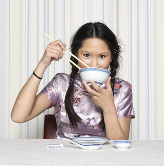 Young woman eating with chopsticks, portrait - JL00117