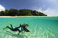 Philippines, Dalmakya Island, woman scuba diver in sea, underwater view - GNF00789