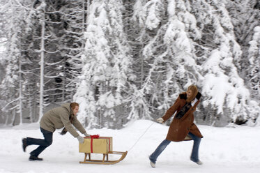 Young couple with sledge and Christmas gift, side view - HHF00461