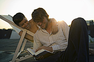 Young woman sitting in deck chair while man reading book - WEST01504