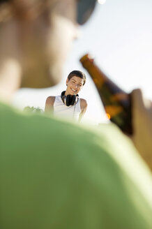 Young woman with headphones while man standing with beer bottle - WEST01471
