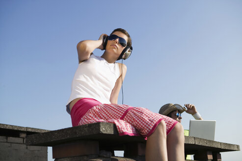 Young man using laptop while woman listening to music, low angle view - WEST01465