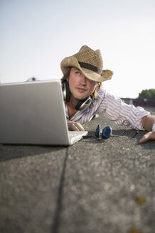 Young man lying by laptop, wearing hat - WEST01459
