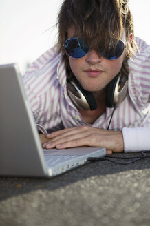 Young man lying by laptop, wearing sunglasses, close-up - WEST01456