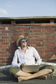 Man using laptop, sitting by wall - WEST01450