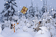 Couple in snow throwing gift at each other - HHF00559