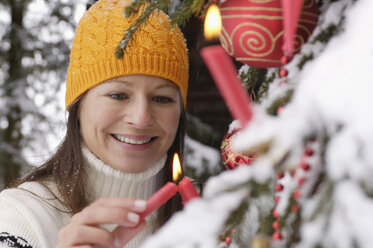 Young woman decorating Christmas tree in snow, smiling - HHF00538