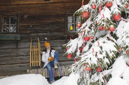 Woman sitting in front of mountain shelter, looking at Christmas tree - HHF00532
