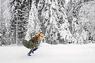 Man in snow, carrying Christmas tree - HHF00529