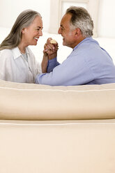 Mature couple sitting on sofa, smiling, side view - WESTF01923
