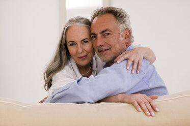 Mature couple embracing on sofa, close-up, portrait - WESTF01887