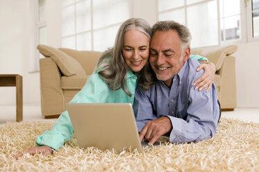 Mature couple lying on carpet, using laptop, smiling - WESTF01878
