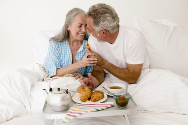 Mature couple sitting on bed with breakfast, smiling - WESTF01875