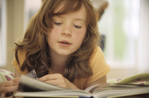 Girl (8-9) reading book, close-up - NHF00232