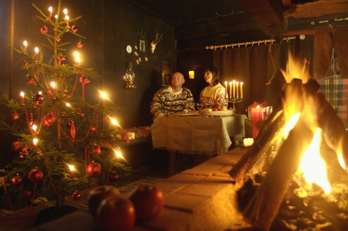 Couple sitting at table in alpine hut looking at Christmas tree - HHF00750