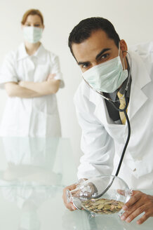 Doctor examining piggy bank - 00103LR-U