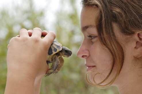 Teenage girl holding turtle, close-up - CRF00969