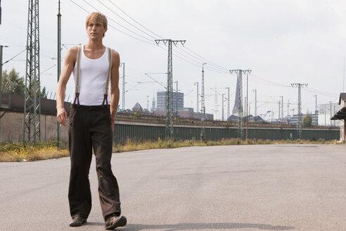 Man walking, power poles in background - ND00068