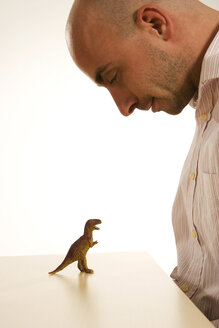 Man looking at toy dinosaur on table - LD00178