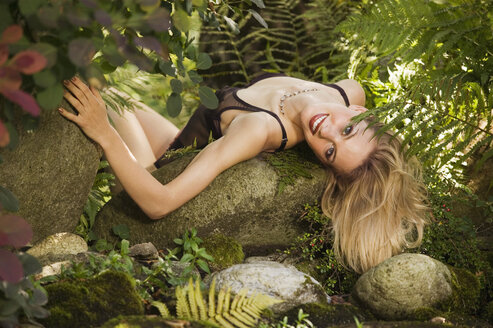 Young woman lying on rocks - AB00045