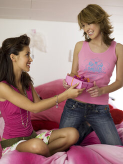 Two teenage girls (16-17) on bed, holding gift - KMF00433
