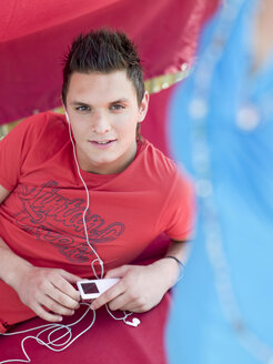 Young man listening to MP3 player, portrait - KMF00339