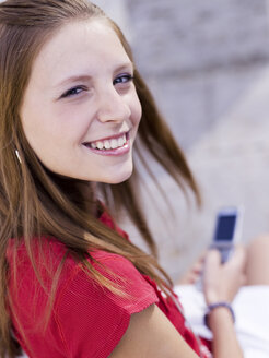 Teenage girl using handy, portrait - KMF00333