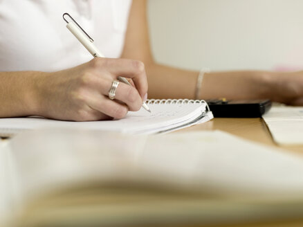 Teenage girl (16-17) writing, focus on hand, close-up - KMF00327