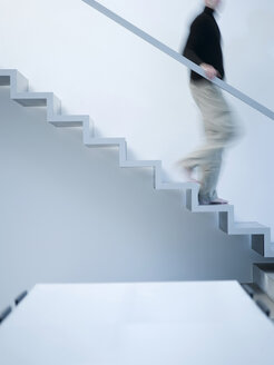 Man moving down stairs, side view - KM00499