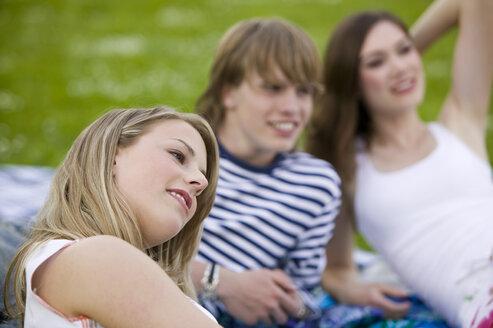 Teenagers lying on picnic blanket - KMF00272