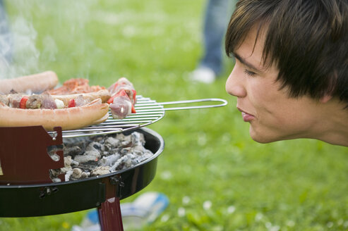 Young man by grill with meat, side view, close-up - KMF00266