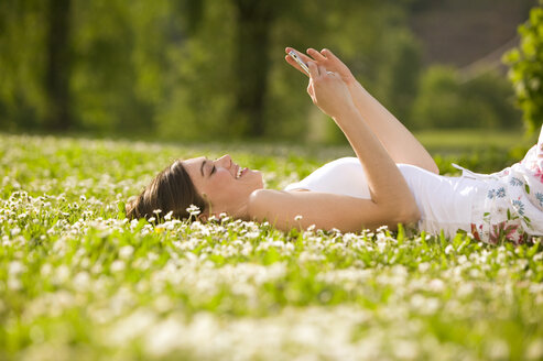 Young woman lying in meadow, holding mobile phone, side view - KMF00254