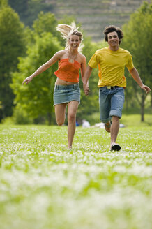 Young couple running in meadow with hand in hand - KMF00218