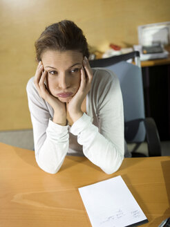 Tired woman sitting at desk, head in hands, close-up - WESTF02690