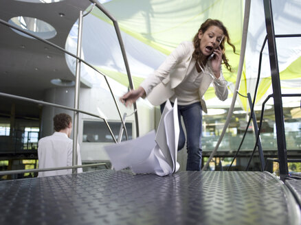 Young businesswoman using mobile phone, papers falling on floor - WESTF02674