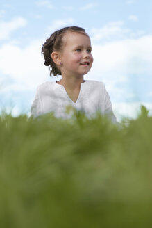 Girl (7-9) sitting in meadow, smiling, close-up - LDF00356