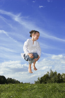 Girl (7-9) jumping in meadow - LDF00347
