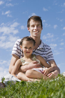 Father sitting with daughter (7-9) in meadow, portrait, close-up - LDF00329