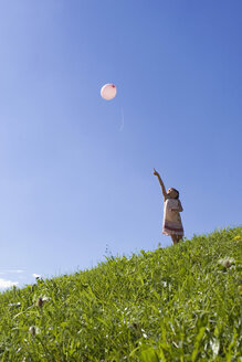 Girl (6-7) standing in meadow pointing at balloon in air, low angle view - LDF00317