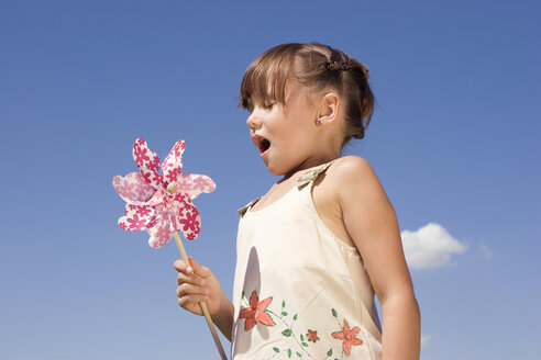Girl (7-9) drawing breath, holding pin wheel - LDF00308