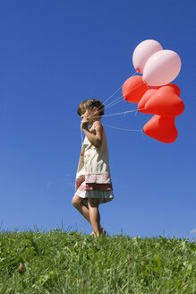 Girl (7-9) holding bunch of ballons, side view - LDF00290