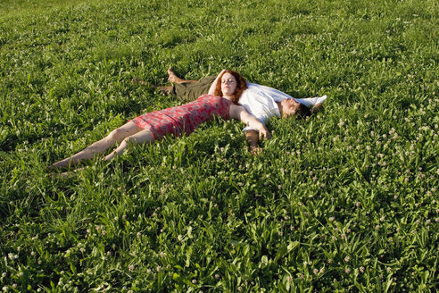 Woman lying with head on man`s belly in meadow - LDF00248