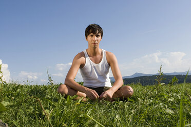 Young man sitting in meadow - LDF00236
