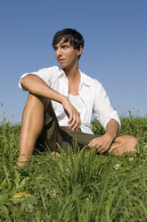 Young man sitting in meadow - LDF00224