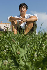 Young man sitting in meadow - LDF00209