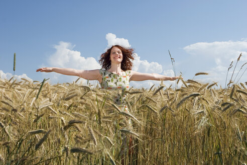Young woman standing in cornfield, arms outstretched, smiling - LDF00203