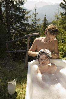 Young woman lying in bathtub, young man washing hair - BABF00156