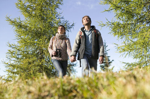 Young couple walking in meadow holding hands - BABF00108
